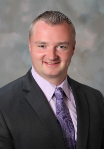 Photo of Greg Ross - a man wearing a suit and tie