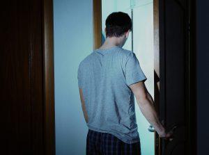 Young sleepy man closing his door