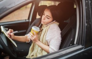 Woman sitting in her car, drinking a beverage, writing in a notebook and talking on the phone at the same time.
