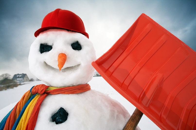 Snowman in a baseball hat holding a shovel