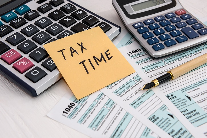 Tax time' memo on tax form next to a calculator