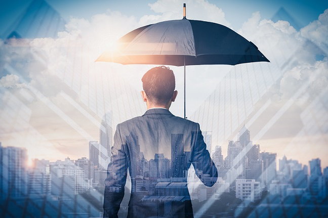 Man looking at a city skyline holding an umbrella